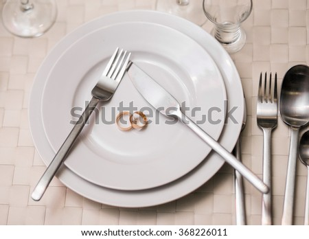 two rings on a plate with serving fork, spoon, knife. The concept of a wedding celebration at Banquet, restaurant