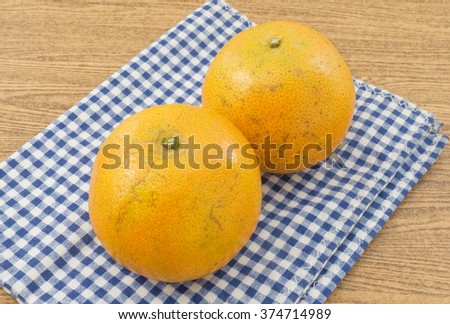 Two Ripe and Sweet Oranges on Wooden Table, Orange Is The Fruit of The Citrus Species. - stock photo