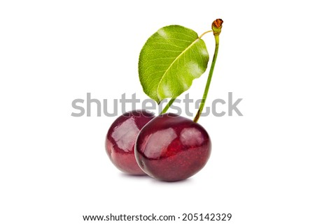 Two ripe, juicy, delicious sweet cherry and green leaves isolated on white background