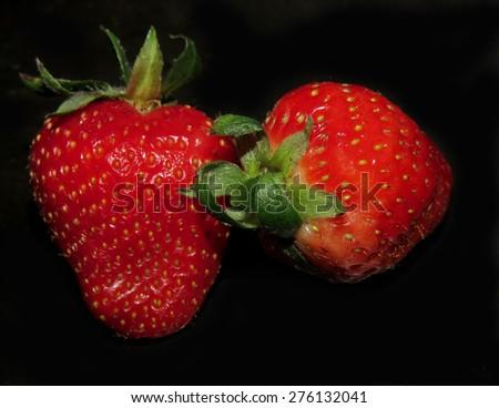 Two ripe organic strawberries on black background - stock photo