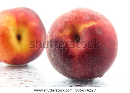 two ripe peaches in the water droplets on white background