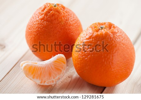 Two ripe tangerines and their segment, close-up, studio shot