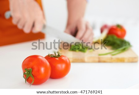 Two ripe tomatoes in the foreground . Man cutting ripe vegetables on a wooden board in the background .
