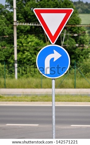 Two road signs on a metal rod on the road