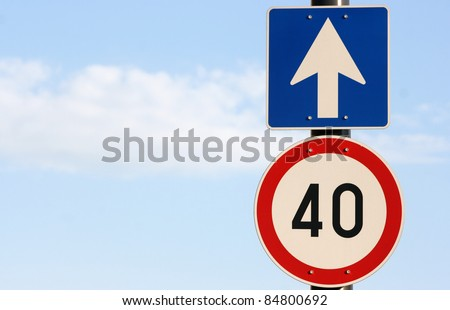Two road signs on post against blue sky represent direction and speed limit (lot of copy space for designers) - stock photo
