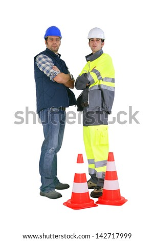 Two road workers stood by traffic cones - stock photo