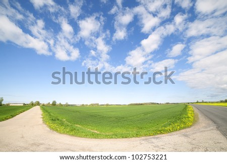 Two roads, field and clouds - stock photo