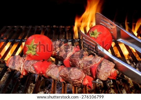 Two Roasted BBQ Beef Kabobs And Tomato On The Hot Flaming Grill Close-up. Tasty Snack For Picnic or Outdoor Party. - stock photo