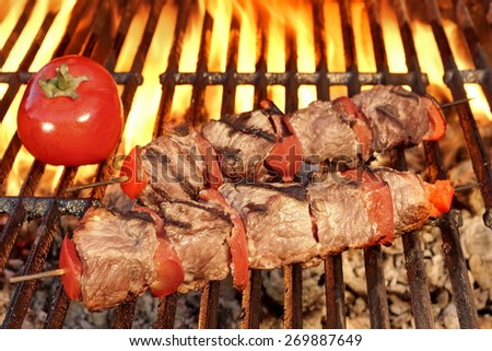 Two Roasted BBQ Beef Kebabs And Tomato On The Hot Flaming Grill Close-up. Tasty Snack For Picnic or Outdoor Party. - stock photo