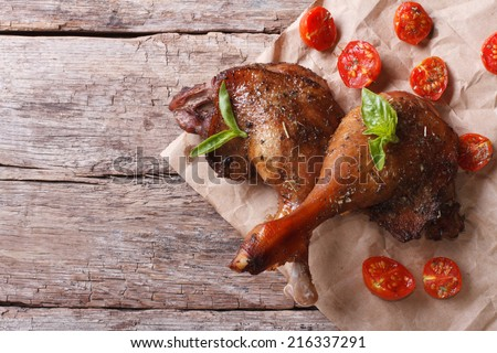 two roasted duck legs with basil and tomatoes close up on an old table top view horizontal  - stock photo