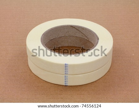 Two rolls of new masking tape on cardboard background. - stock photo