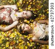 Two romantic girl lying in autumn leaves - stock photo
