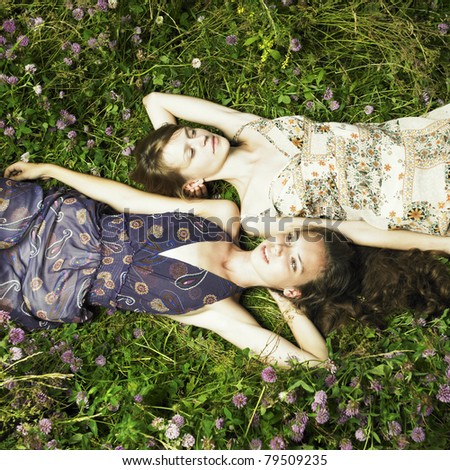 Two romantic girl lying on flower meadow - stock photo