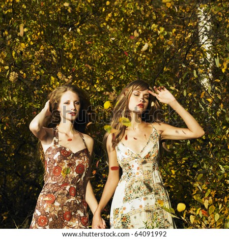 Two romantic girl surrounded by autumn leaves - stock photo