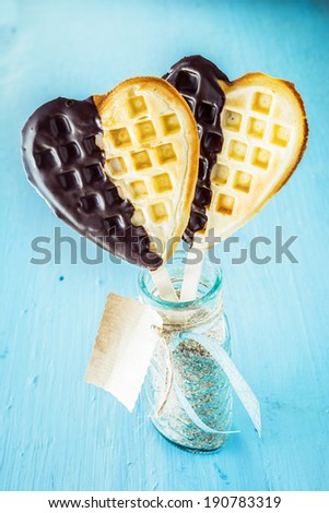 Two romantic heart shaped golden waffles dipped in chocolate symbolic of love on a stick in a glass jar with gift tag for a sweetheart on a special occasion or celebration - stock photo