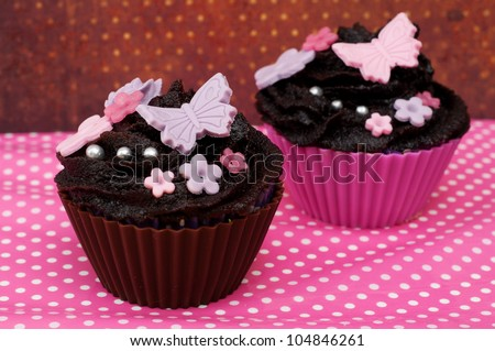 Two romantic wedding cupcake with flowers and butterfly on a pink dotted background - stock photo
