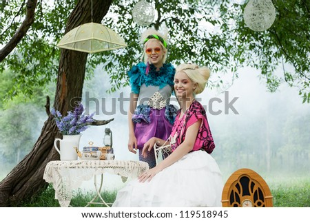 Two romantic women on a picnic in a fairy foggy forest. Outdoors. - stock photo