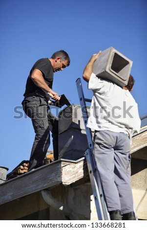Two roofers hard at work - stock photo