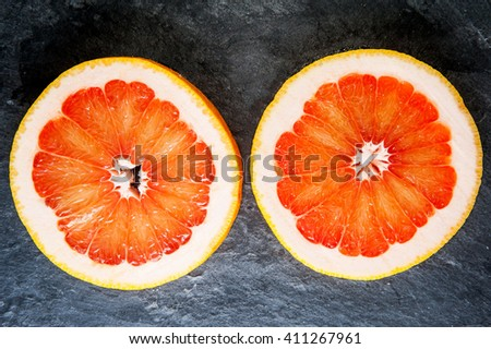 Two round cuts of grapefruit on dark background - stock photo