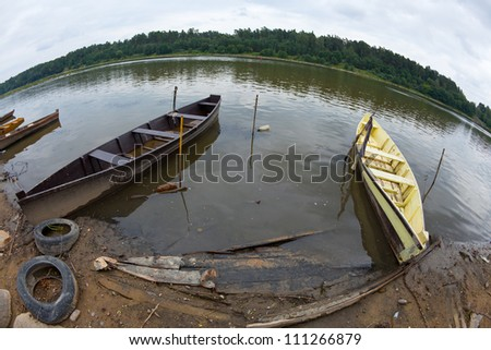 Two rowing boats moored on a river bank with old tires, horizon line bending - stock photo