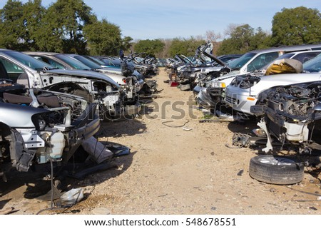 two rows of cars in a salvage yard facing each other