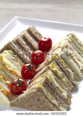 two rows of homemade club sandwiches decorated for a party - stock photo