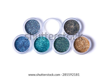 Two rows of metallic glitters in jars, top view isolated on white background  - stock photo