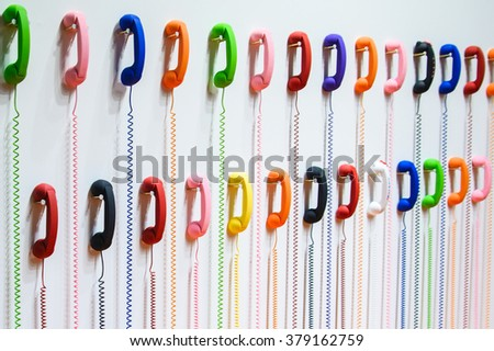 Two rows of multicolored handsets: yellow, blue, pink, green, red, white, orange hanging on a white wall. A spring wire spiral - stock photo
