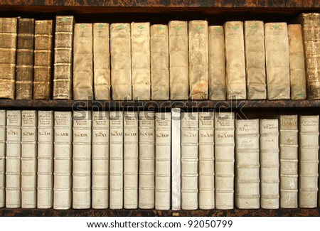two rows of old books on a shelf - stock photo