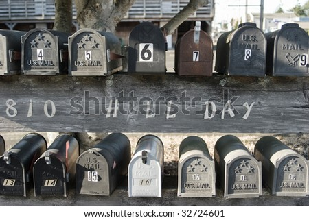 Two rows of U.S. mailboxes sitting on a fence. - stock photo
