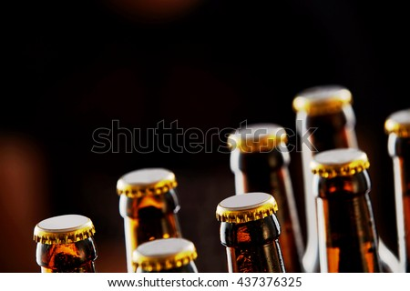 Two rows of unopened brown beer bottles in a closeup diagonal view over a dark background with copy space - stock photo