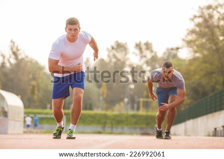 Two runners racing on track - stock photo