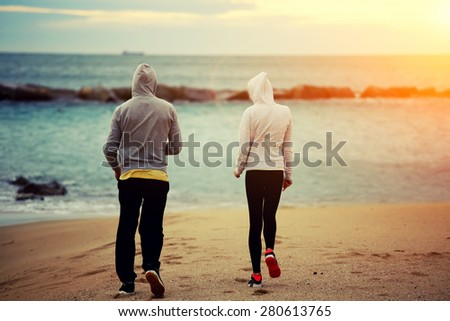 Two runners walking on the beach while they rest after intense morning training, sporty couple of friends taking break after workout outdoors at seashore with beautiful orange sunrise on background - stock photo