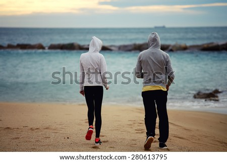 Two runners walking on the beach while they rest after intense morning training, sporty couple of friends taking break after workout outdoors at seashore with beautiful sunrise on background - stock photo