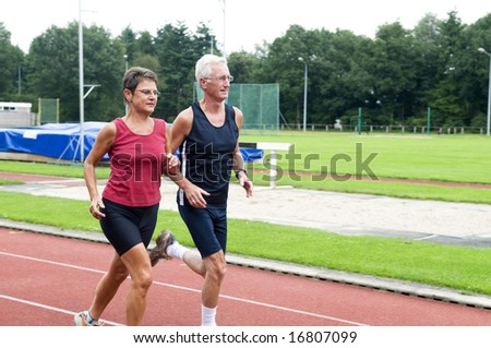 Two running pensioners having a healthy lifestyle. - stock photo
