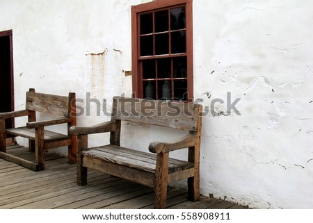 two rustic benches set against white stone exterior wall of building invite people to sit and