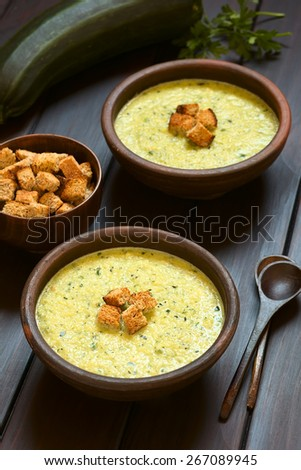 Two rustic bowls of cream of zucchini soup with homemade croutons on top, photographed on dark wood with natural light (Selective Focus, Focus on the croutons on the first soup) - stock photo