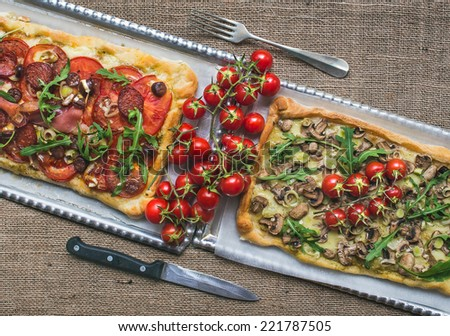Two rustic square pizzas with fresh arugula and cherry-tomatoes on silver trays over a sackcloth background - stock photo