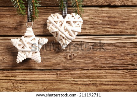 Two rustic straw Christmas ornaments on a textured wooden background with copyspace with a symbolic star and heart for a seasonal greeting for loved one - stock photo