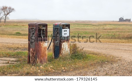 two rusty old abandoned gas pumps  - stock photo