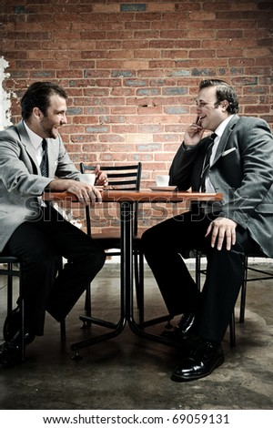 two 70's styled men laugh together while meeting up for coffee, vintage style - stock photo