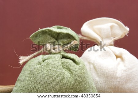 Two sacks filled with green and white corded