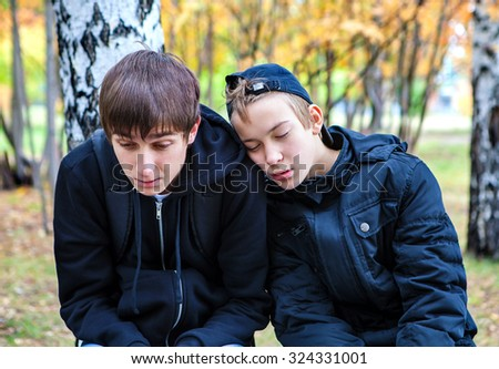 Two Sad and Tired Boys in the Autumn Park