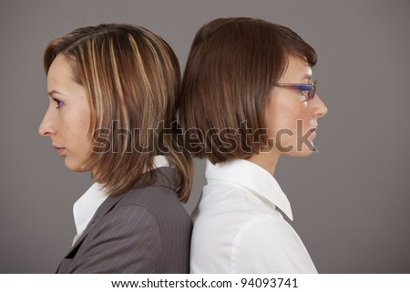 two sad business women standing back on back over grey background