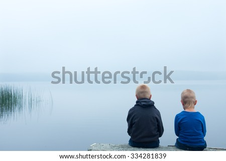Two sad children (boys, brothers) sitting alone by lake in a foggy day, back view - stock photo