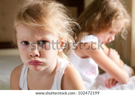 two sad girls on the bed - stock photo