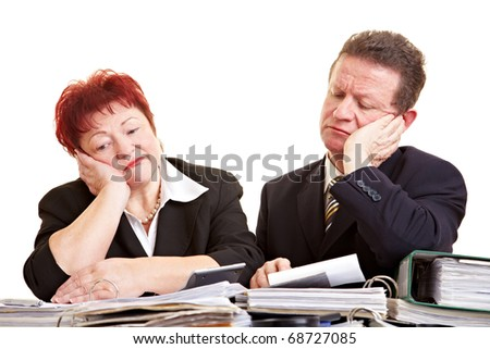 Two sad senior people with files on a desk