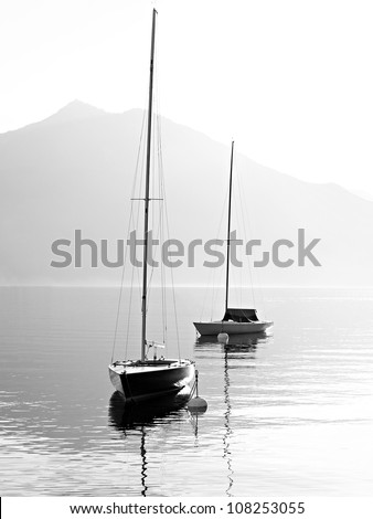 Two sail boats in early morning on the mountain lake. Black and white photography. Salzkammergut, Austria. - stock photo