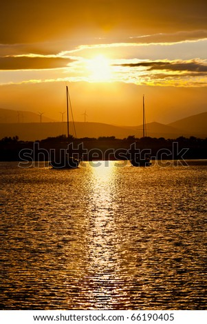 two sailboats anchored at sunset - stock photo