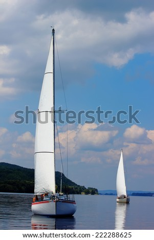 Two sailboats on peaceful still waters in a harbor.